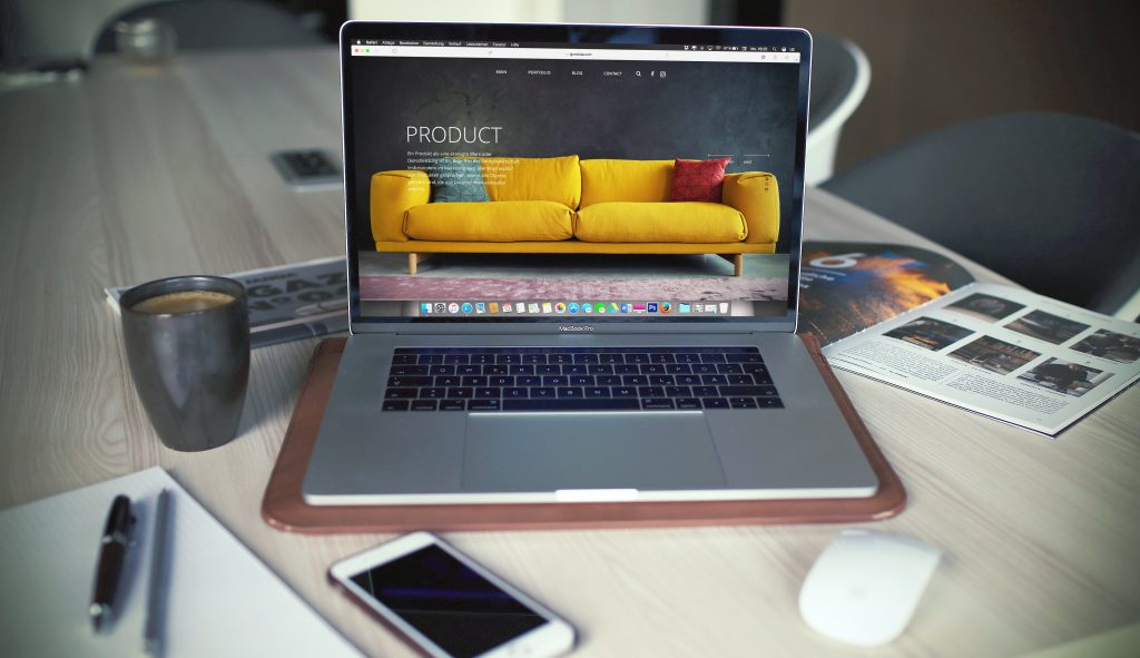 """A laptop displays a stylish webpage promoting a couch for sale with the text """"PRODUCT"""" visible."""