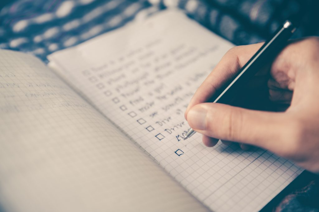 A person fills out a checklist in their rebranding guide.