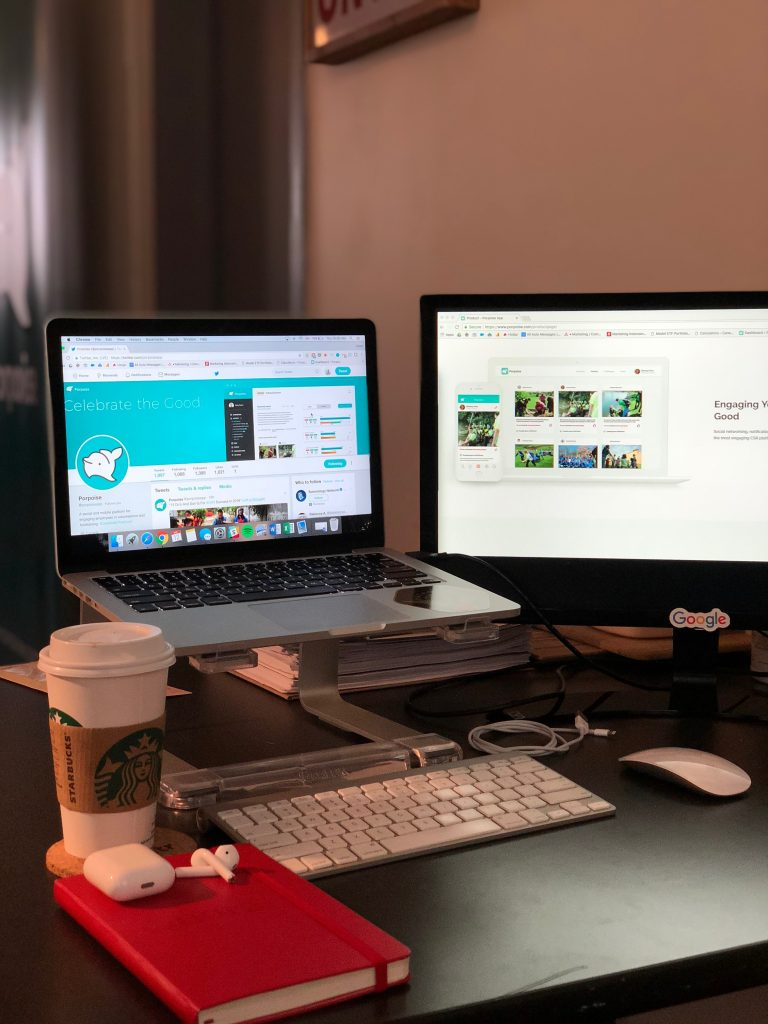 The office workspace of a social media marketer, featuring a laptop opened to Twitter, a coffee cup, an extra monitor, and a notebook.