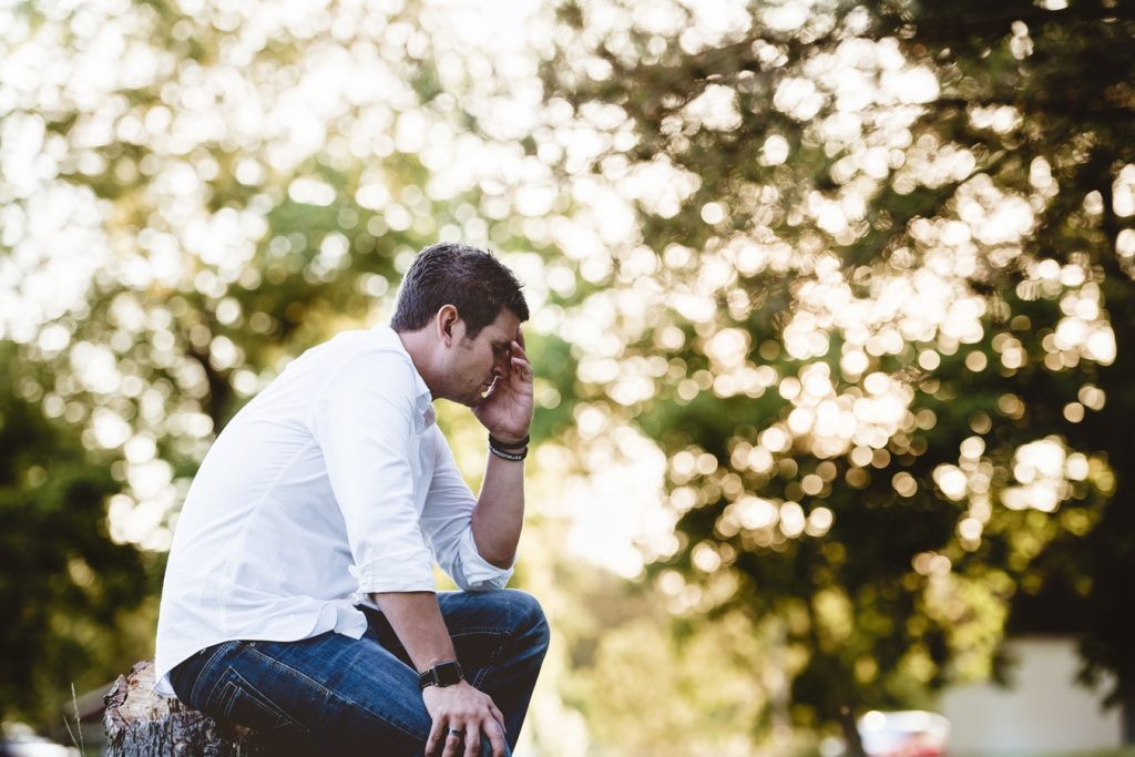 A man in a white shirt sits outdoors, holding his head in his hand in stress or frustration.