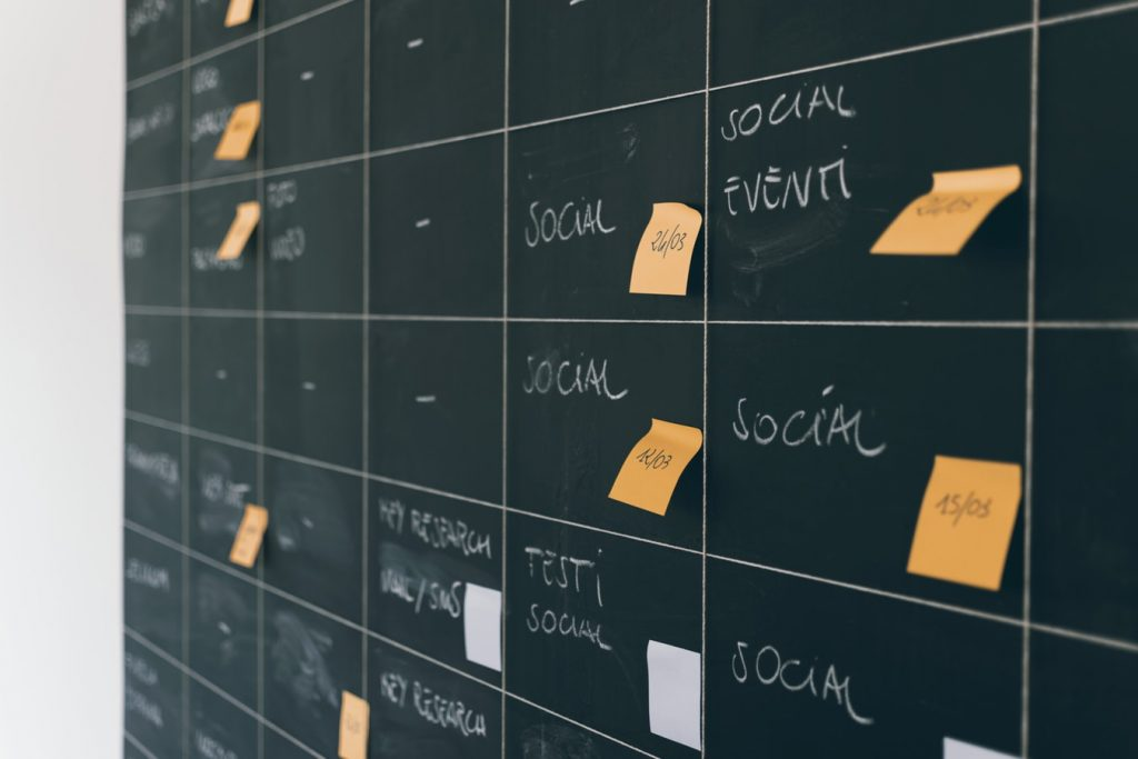 A blackboard with various social media markings on it is covered with stick notes with dates and times.