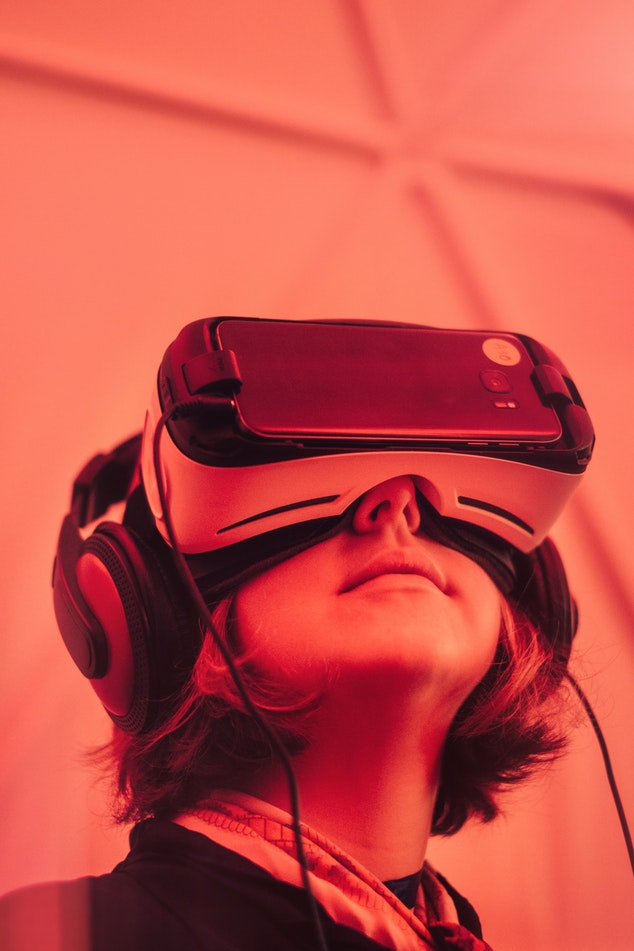 A young woman wears a set of VR goggles.
