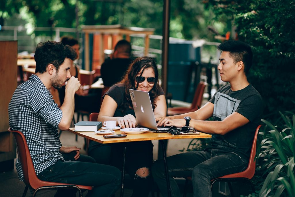 Three young people sit around a cafe's patio table, smiling as they look at a laptop.