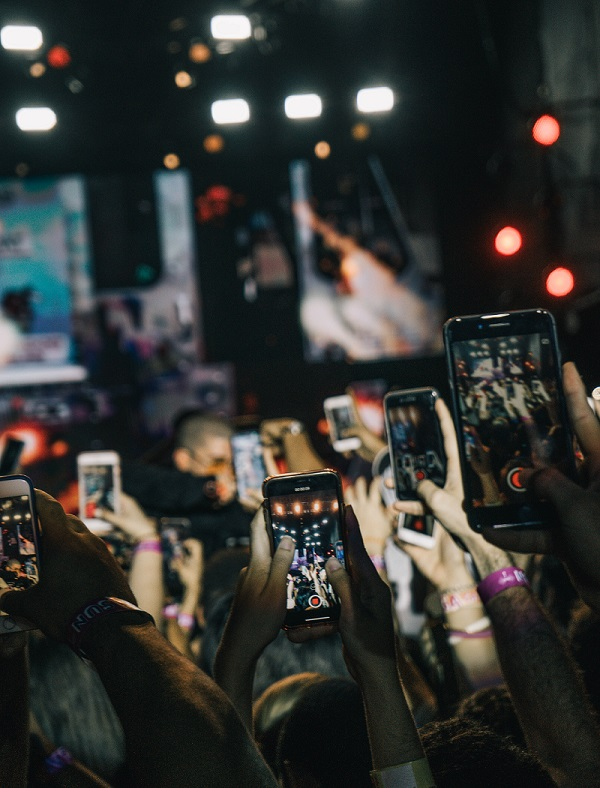 Hundreds of people take videos on their smartphones at a concert