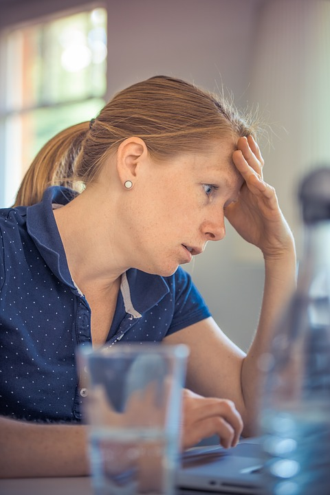 A woman holds her head in shock as she stares at her laptop.