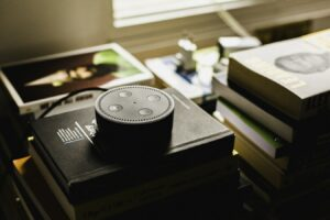 A smart home speaker sits on a pile of books