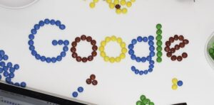Google logo made out of M and Ms candies laid out on a desk.
