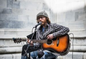 Busker playing acoustic guitar