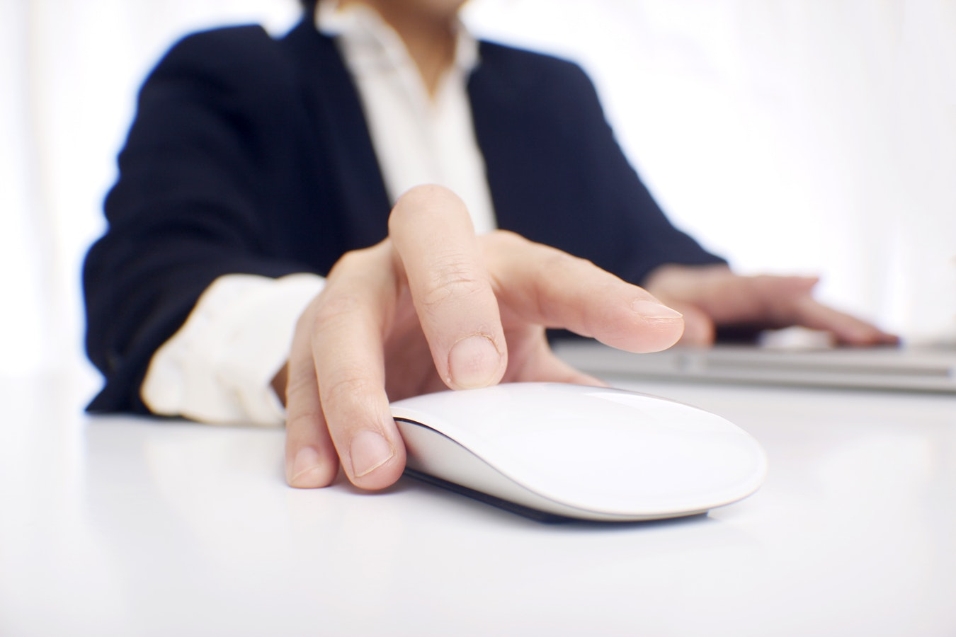 A person clicks on a wireless mouse.