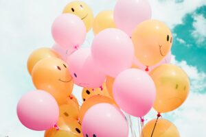 yellow and pink balloons with smiley and frownie faces