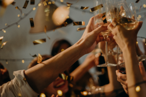 People clinking wine glasses as gold confetti floats in the air