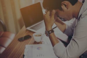 Frustrated man in front of computer and papers with hand on his forehead