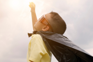 Little boy wearing goggles and superhero cape pointing towards the sky