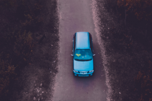 Blue car driving on country road