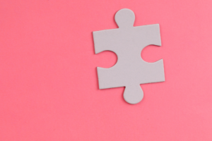 White puzzle piece on pink background