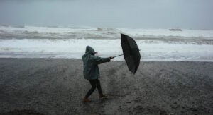 Man in storm trying to hold onto umbrella